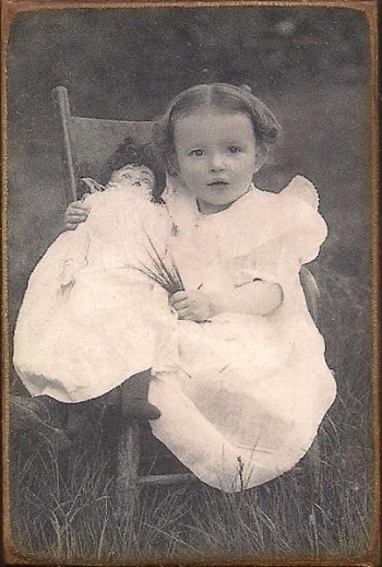 Antique photo of a little girl with her doll, circa 1900.