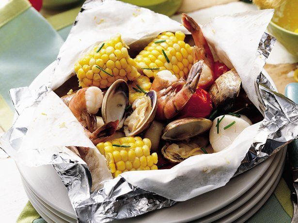 Looking for a grilled seafood recipe? Then check out this shrimp, scallops and vegetables packs drizzled with butter – a wonderful dinner topped with chives.