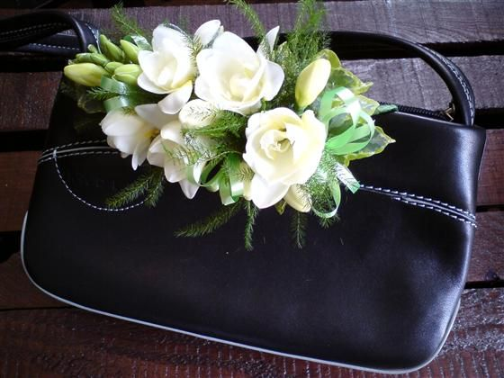 Handbag Corsage - not crazy about the purse but the flowers are lovely. If making it as a DIY project, ensure the purse is fabric that can taken the pinning necessary to hold flowers in position - or attach a 'loop' of open two-ended satin ribbon as part of the backing of corsage so it can be tied onto the handle of a purse
