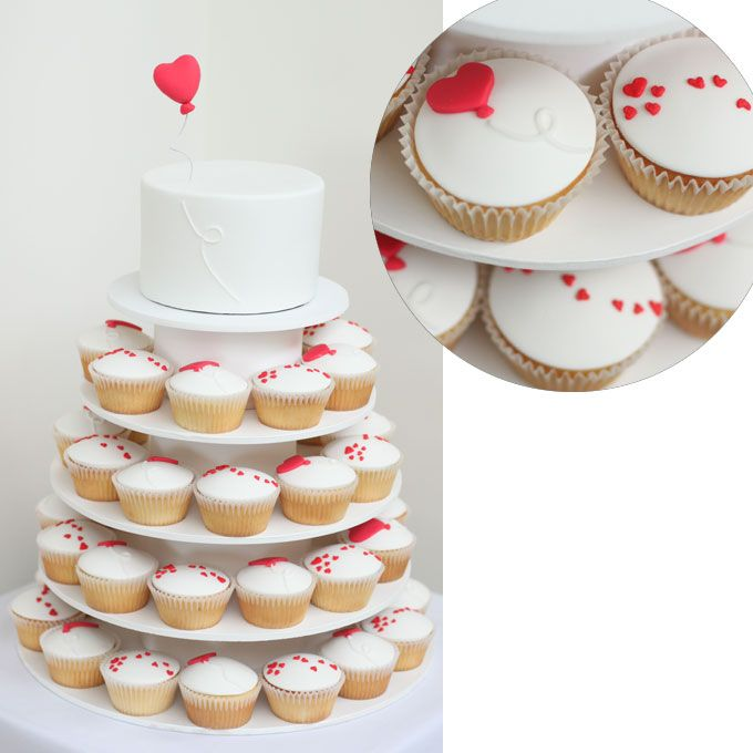 Brides: White Cupcakes with Scattered Hearts. When applied to a clean background of white fondant, scattered red hearts and heart-shaped balloons provide a strong graphic element that feels surprisingly modern.