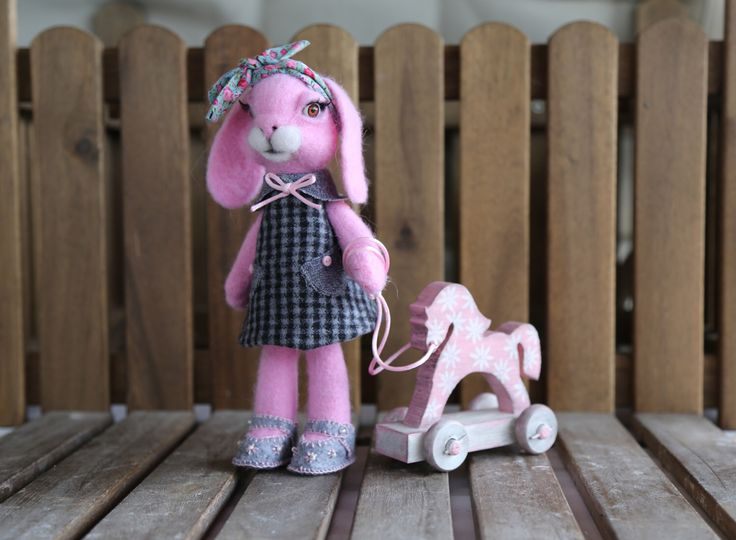 """Needle felted pink bunny. Easter bunny. Wool bunny with pink horse. Easter hare. Collectible needle felted doll """"Bunny with wooden horse"""" by donidinadya on Etsy https://www.etsy.com/listing/514314845/needle-felted-pink-bunny-easter-bunny"""