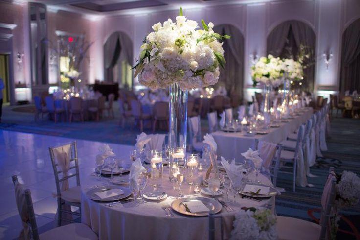 all white, ballroom, silver chivari chairs, wedding reception  featuring beautiful tall flower arrangements