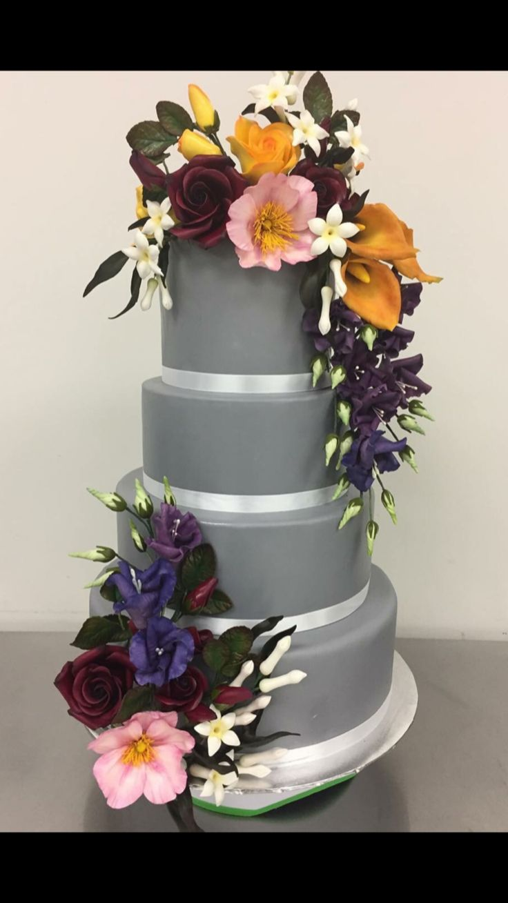 Large grey wedding cake or perhaps for a silver wedding anniversary, beautifully decorated with white satin ribbons and colorful flowers.