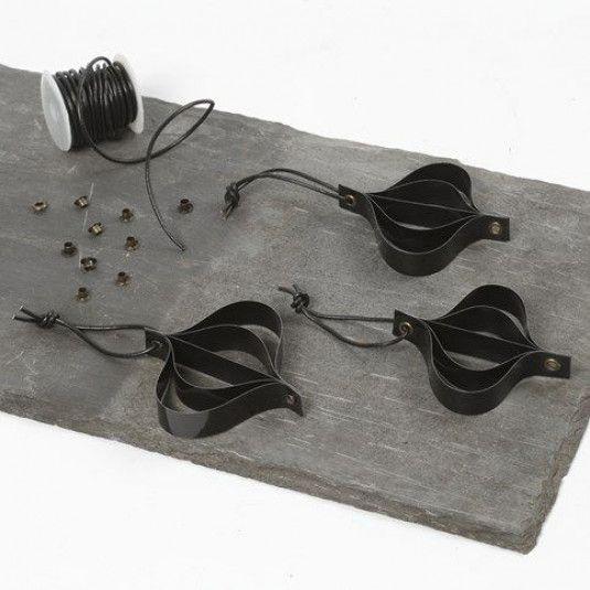 Hängende Dekorationen aus schwarzen Fröbelsternstreifen mit Lederschnur