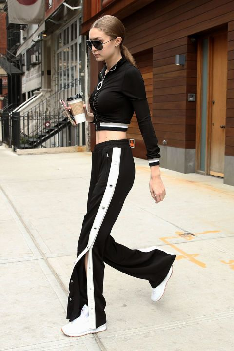 In a cropped black and white track jacket, matching tearaway track pants, white Reebok sneakers and black aviator sunglasses while leaving her apartment in NYC.