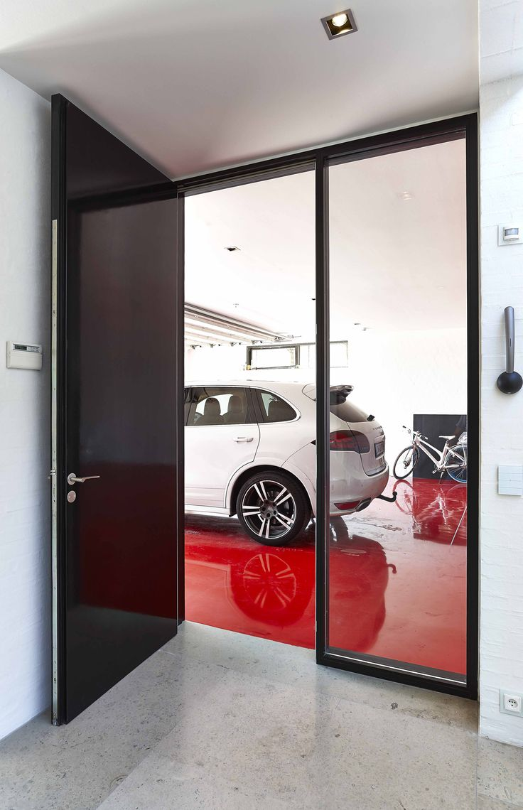 A glossy door with a Porsche stored on the red floor. This is a project for a private man.