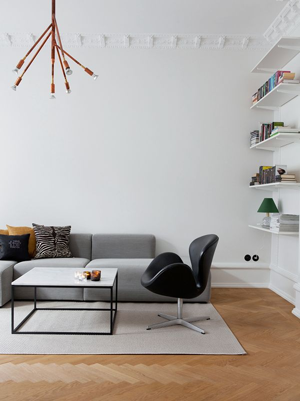 Minimal living room with marble coffee table, 'Swan' chair by Arne Jacobsen & simple wall shelves