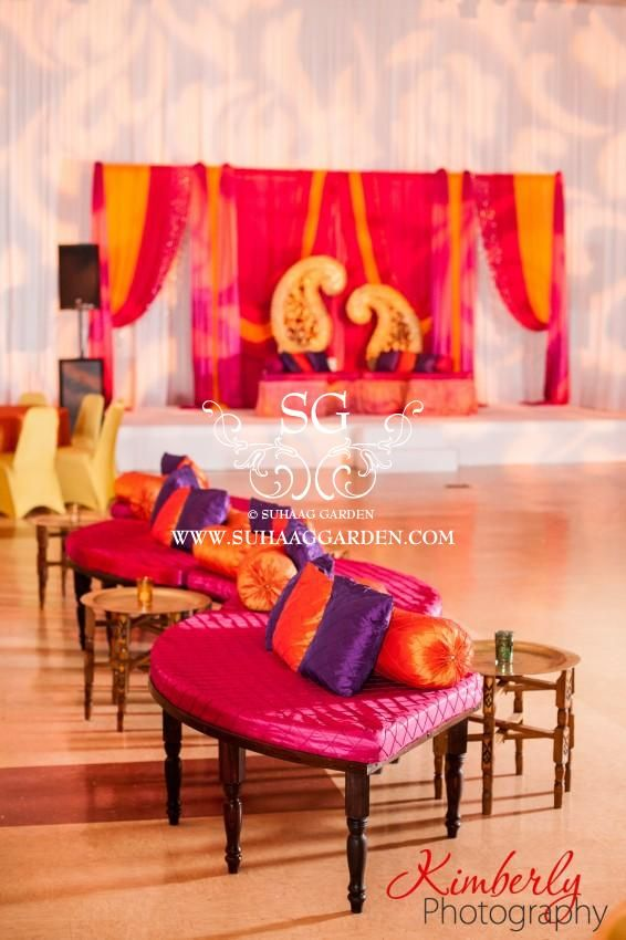 Suhaag Garden, Florida Indian wedding decorator, Mehndi stage, paisley backdrop, throw pillows, serpentine cushioned benches