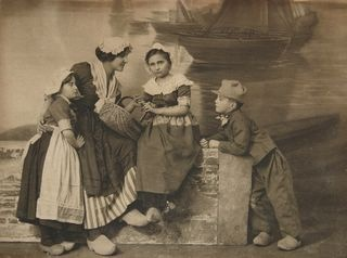 Dutch maid & children in historic costumes and wooden shoes; studio-photo ca 1900.