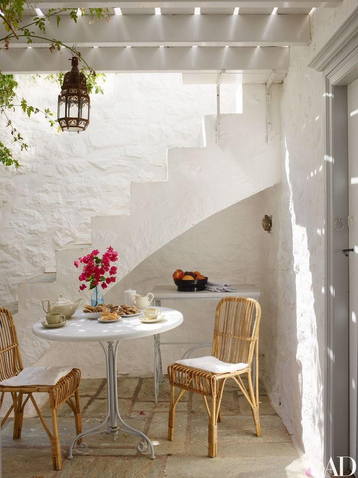 In the breakfast area off the kitchen, wicker chairs by Liggestolen are pulled up to a 19th-century marble-top wrought-iron table.