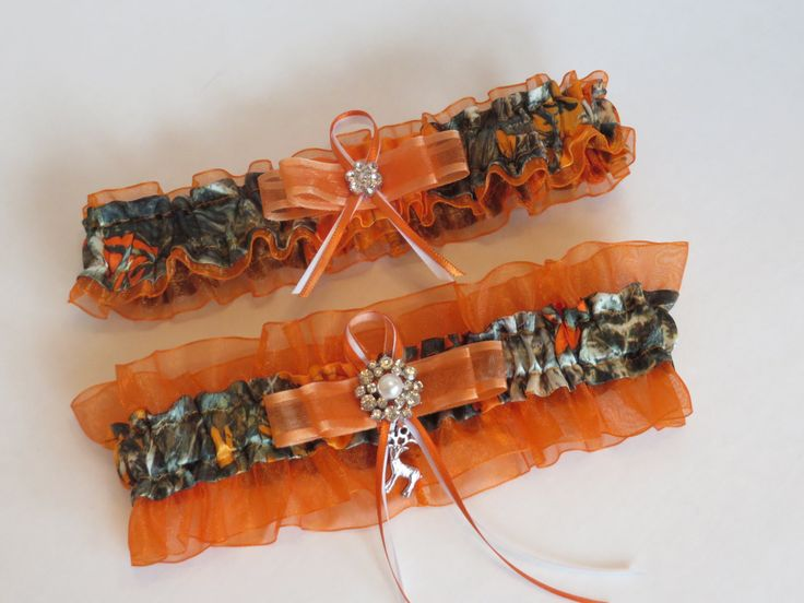 This adorable garter set is True Timber Satin Orange Blaze Camo print. They are embellished with orange and white organza and satin ribbons and accented with a pearl and rhinestone brooch. Choose a ch