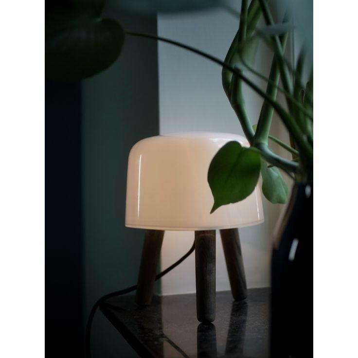 Lampe à poser Milk - Brun - Ø20cm - And Tradition  Lumi-Design Avec son joli trépied en bois teinté, la lampe MILK de la marque danoise And tradition est un luminaire résolument empreint de la tradition scandinave. Comme son nom l'indique, elle nous transporte dans les pâturages. Ses courbes s'inspirent de la forme d'un tabouret à trois pieds que l'on utilisait pour traire les vaches. Son abat-jour en verre soufflé à la bouche est non sans rappeler la couleur du lait.