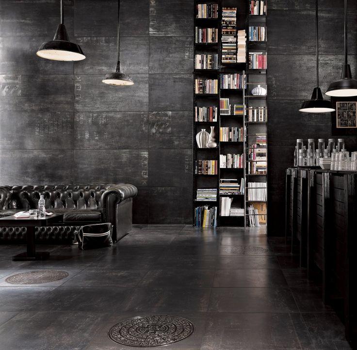 dark, dark, dark. Chesterfield, bookcase, farmhouse lights, stone wall stone floor