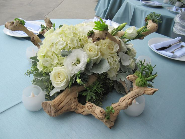 Each centerpiece was unique based on grapevine base to look like drift wood. Roses, hydrangea, lizianthus, lamb's ear and succulents.