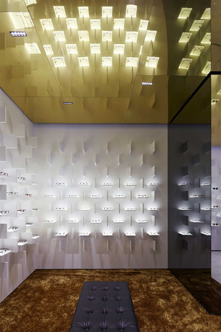A combination of horizontal shelves, a gold ceiling & LEDs dramatically illuminate the glasses within Bolon Eyewear's flagship store by Ippolito Fleitz.