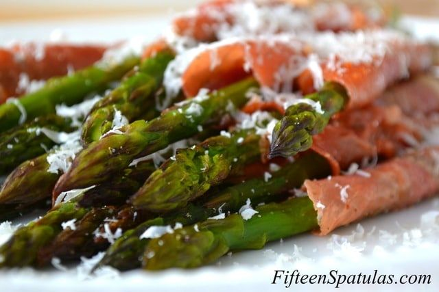 Prosciutto wrapped asparagus is a beautiful classic dish that a fair amount of you may be familiar with, but for those of you who haven't had it, you need to try it, and put my little twists in there!  Vegetables sometimes need a little bit of help, and this is a good way to get the pickiest eaters on board with asparagus.   I lay out long strips of prosciutto and grate some parmigiano reggiano over it.  Roll the asparagus spears with the parmigiano prosciutto and bake until the prosciutt...