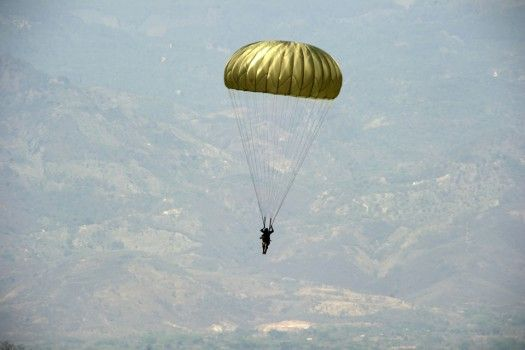 Photo: A Honduran Paratrooper, assigned to 2DO. Batallon De Infanteria Aerotransportado, maneuver towards the drop zone during a partner nation static line jump with Soldiers from 7th Special Forces Group (Airborne) Soto Cano Air Base, Honduras., April. 03, 2014. (U.S. Army photo by Spc. Steven K. Young/Released)