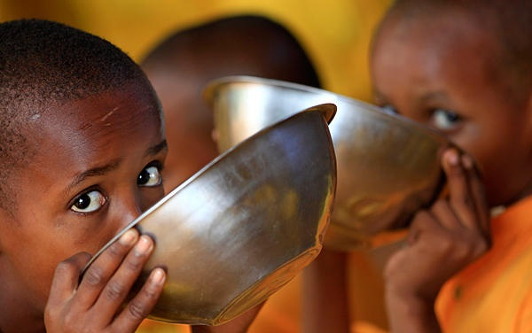 Somali refugee boys eat porridge at the Liban integrated academy at the Ifo refugee camp in Dadaab, Kenya, near the Kenya-Somalia border. The United Nations estimates that more than 3.7 million people in Somalia, among them 800,000 children, are on the brink of starvation