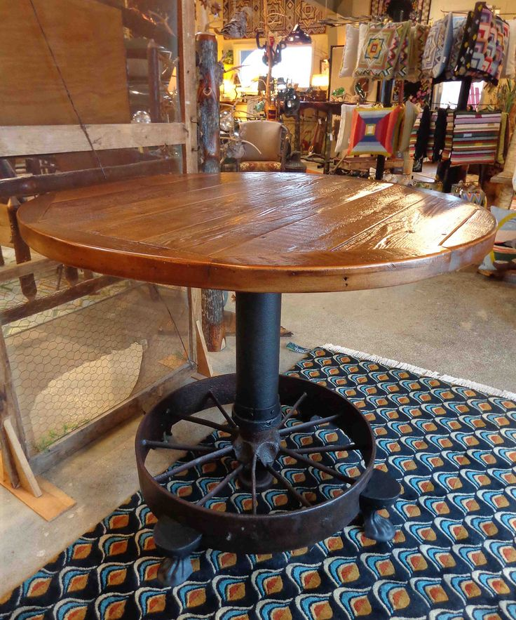 This table was made from a steel wheel, bought at a flea market, that came from a very old steam tractor. Notice the legs; they are from an old cast iron bath tub. This piece was a collaboration between Normand Pinette, a blacksmith from New Hampton, NH, and Jodi Sleeper, owner of American Cottage.