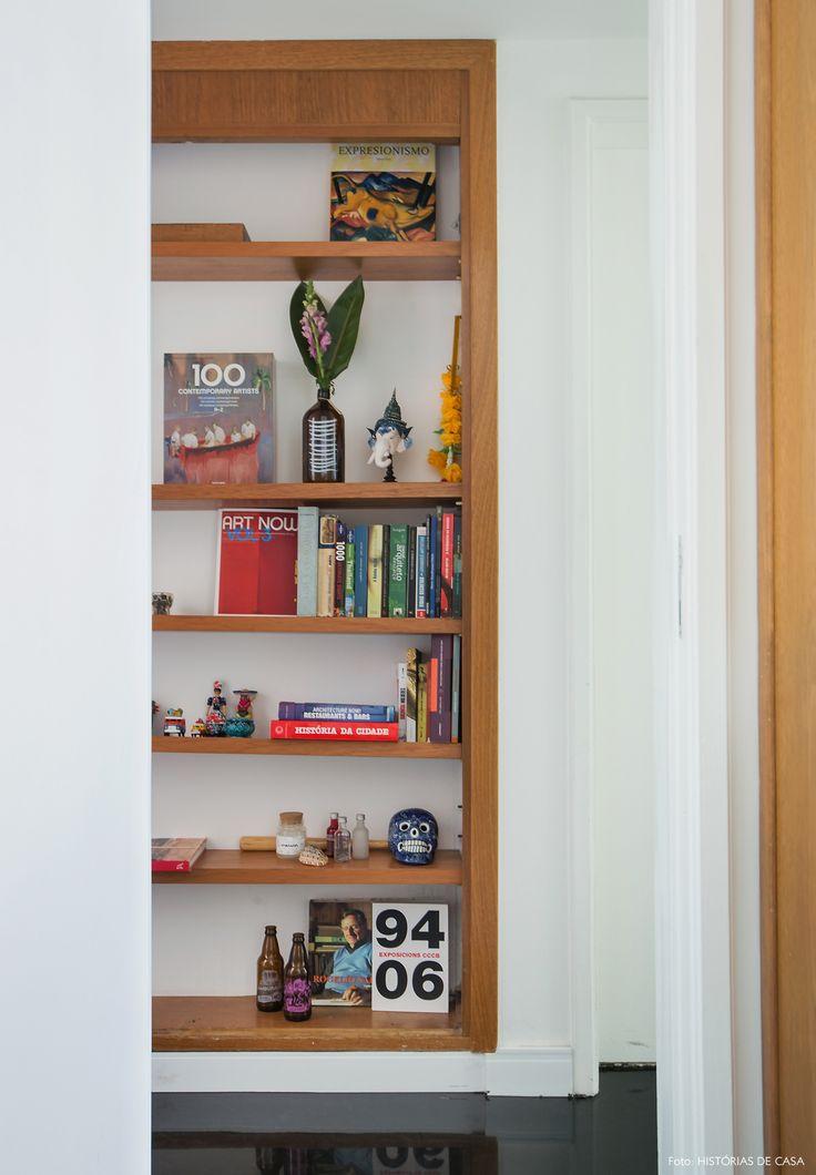 Estante de madeira no corredor abriga livros e objetos de decoração.