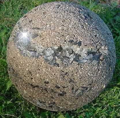 a spiral of broken safety glass embedded in a hypertufa sphere