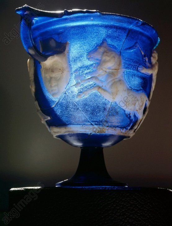 Rare Roman blue glass cameo carved skyphos, depicting a scene from a Greek chariot race. Scholars have suggested it may represent the Dionysiac games or the funeral games of Patroclus described by Homer. View showing horses and mask. Culture: Roman. Date / P (..)