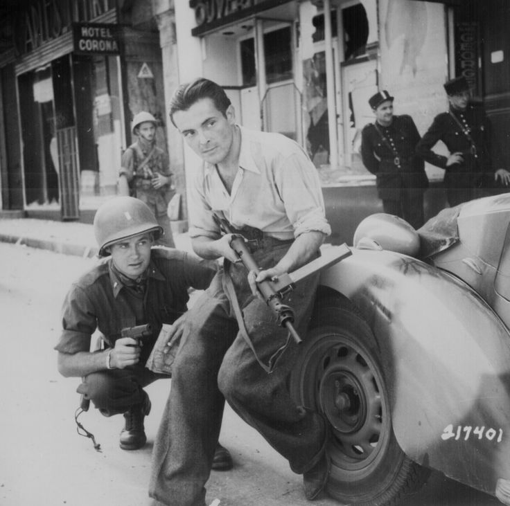 An American officer and a French partisan crouch behind an auto during a street fight in a French city, ca. 1944.