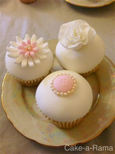 Mothers Day Cupcakes  : These beautiful white fondant topped cupcakes are all hand decorated with pink bows, flowers and buttons, with a tiny edible pearls for a touch of class