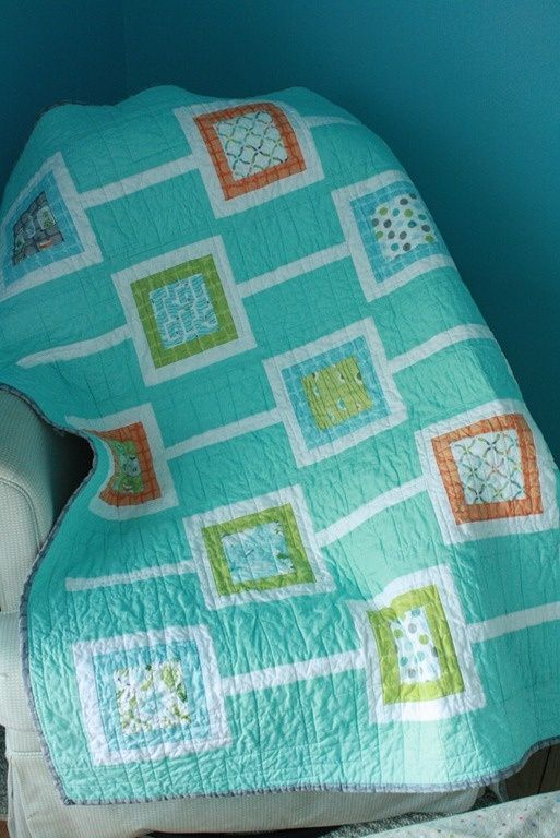 Modern baby quilt with turquoise background fabric.