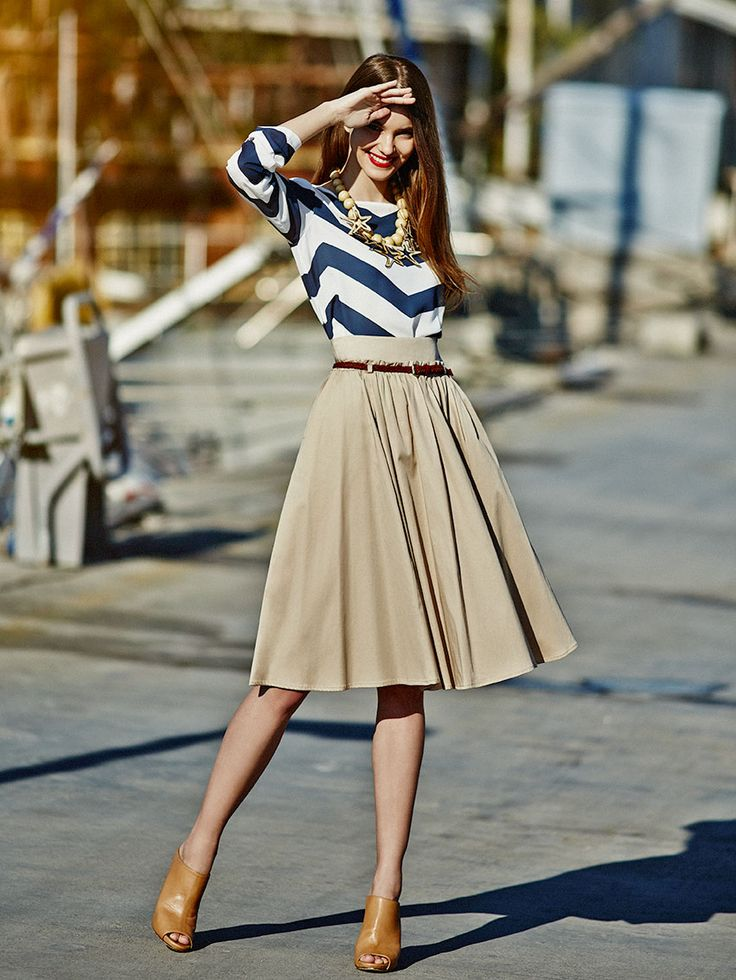 striped blue and white blouse paired with a beige skirt and a thin belt
