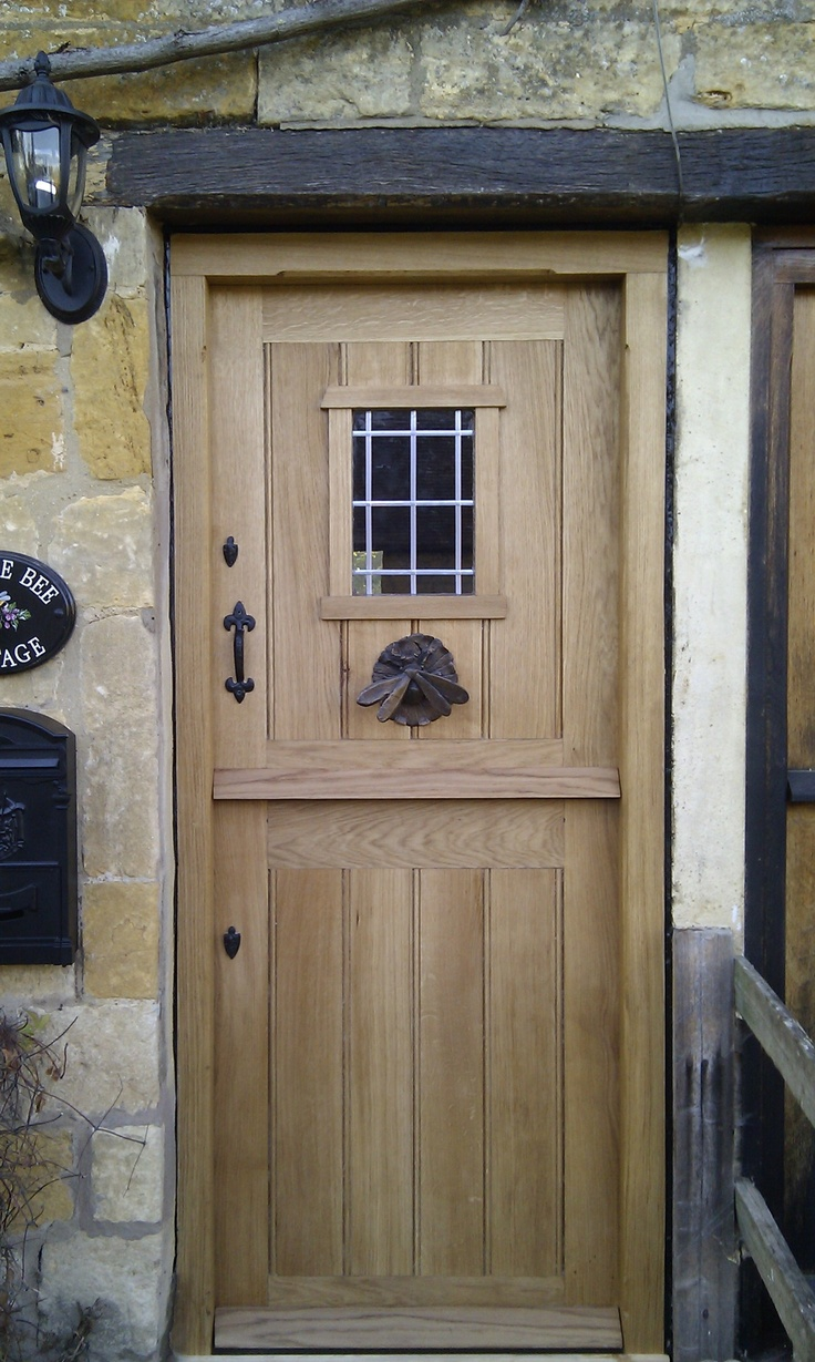 One of our oak doors in place with small window and ironmongery - www.traditionaljoinery.co.uk