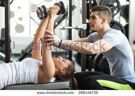 Fitness instructor exercising with his client at the gym. - stock photo