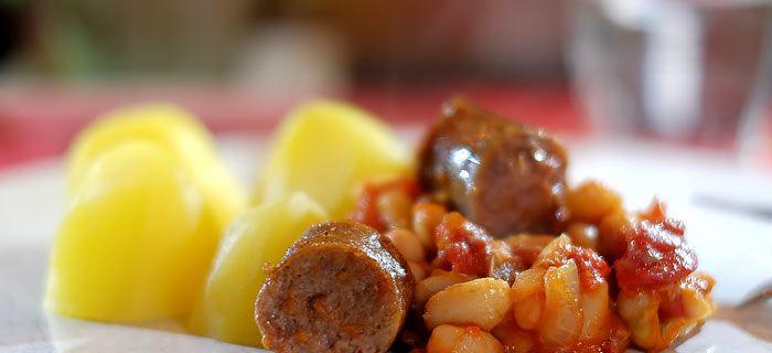 De witte bonen in tomatensaus bereid je deels in de oven. De meegebakken pancetta en stukjes saucijs geven dit gerecht een heerlijke smaak. Hier het recept.