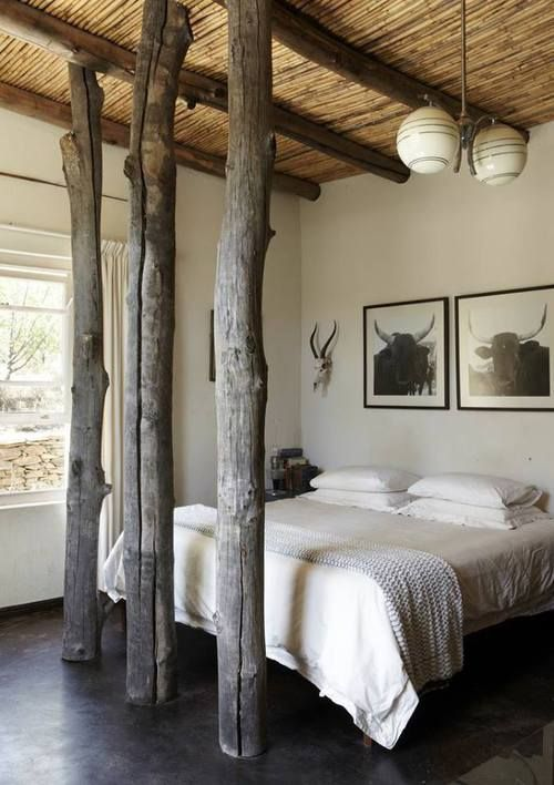 rustic bedroom design with wood beam ceiling details, large tree trunks and cattle wall prints + antlers