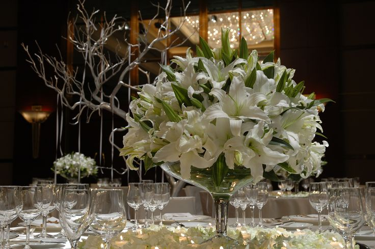 This centerpiece of white Lilies is bursting with life.