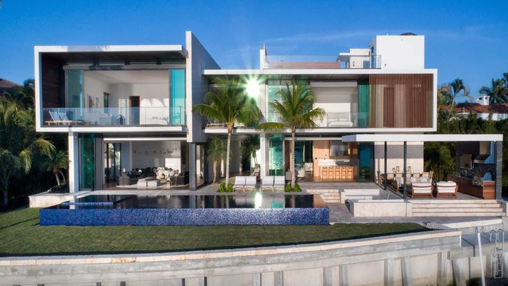 This modern house in Miami has a swimming pool and an outdoor entertaining area with a sunken lounge, outdoor kitchen, as well as an outdoor dining area.
