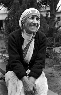 "Mother Teresa laughing;  ""Faith in action is love, and love in action is service. By transforming that faith into living acts of love, we put ourselves in contact with God Himself, with Jesus our Lord."""