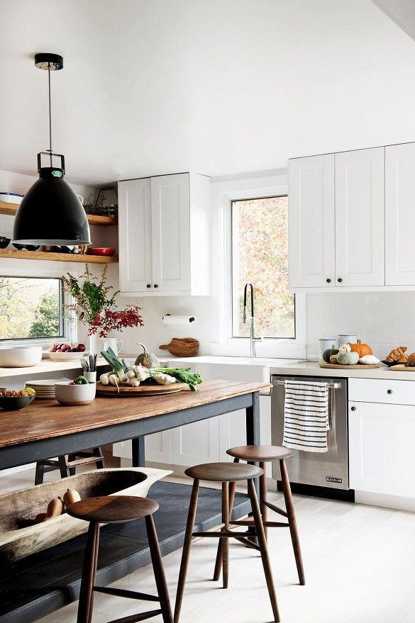 Long table makes this kitchen looks so comfortable and inviting. Black pendant light, white cabinets, wood counter.
