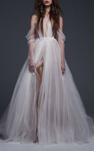 This **Vera Wang** gown rendered in hand draped French tulle features a plunging V neckline, off-the-shoulder draped sleeves, and an A-line silhouette.