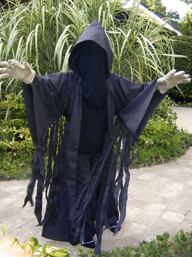 "Very simple Dementor costume. Start with all black clothing. Sew a black ""Jedi"" robe adding extra fabric under arms and shredding it. Make a two layer black nylon bag for the head and buy the plastic hands online.  I also used double sided garment tape to keep the hood in place."