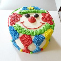 """A buttercream clown smash cake to match the """"Big Top"""" theme of a 1st birthday party. Instructions on how to decorate it included."""