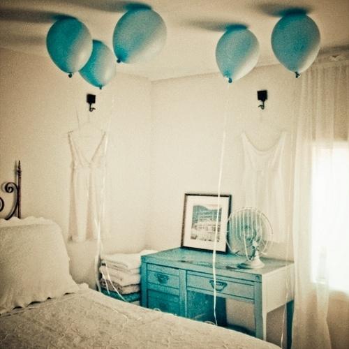 white bed. blue balloons. blue desk.