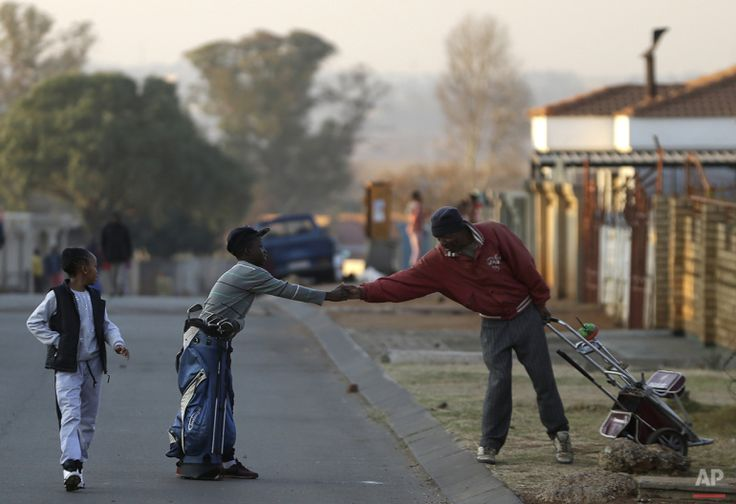 Atlehang Lebeloane, left, shakes hand with his golf mentor Wynand Morudu, right, as they part ways at a park  in Katlehong township, east of Johannesburg, South Africa, Thursday, July 16, 2015. (AP Photo/Themba Hadebe)