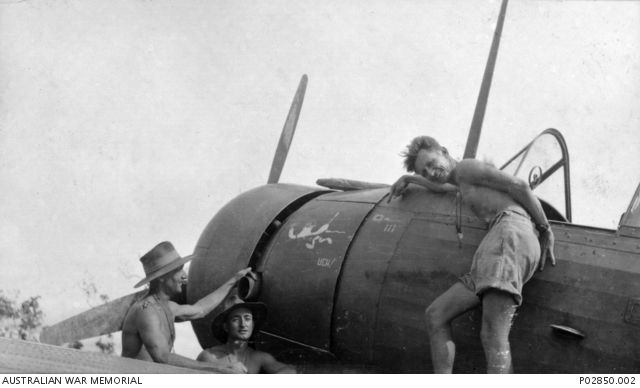 Members of No. 4 (Wirraway) Squadron, RAAF with the Wirraway (A20-103) aircraft that Pilot Officer John S (Jack) Archer was flying when he shot down a Japanese Zero aircraft. Joe Booker is pointing to a Japanese flag that was painted on the nose of the aircraft to commemorate shooting down the Zero.
