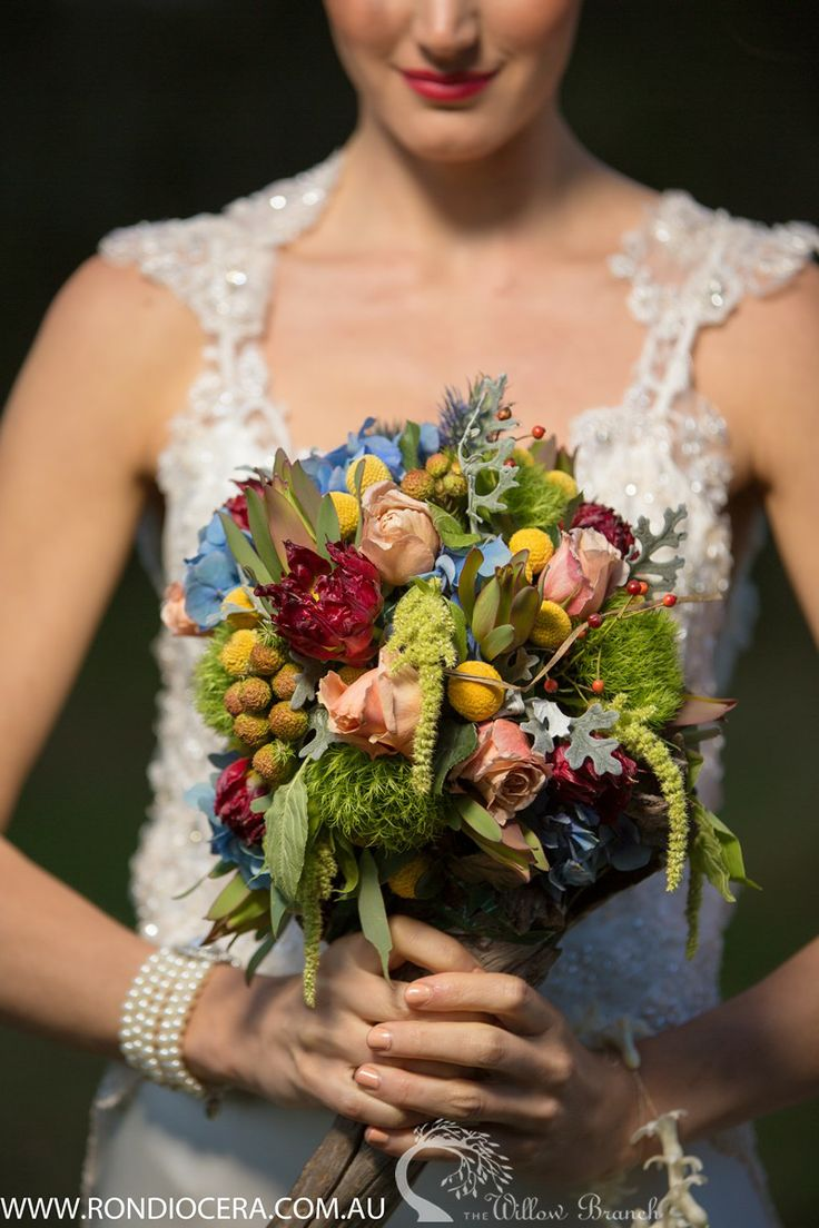 A wide variety of flowers have been used to give a more natural and earthy feel: brunie, hydrangea, billy buttons, hanging amaranth, green trick, soho roses, leucodendron, tulips, sea holly, snowberry and dusty miller foliage.  http://www.thewillowbranch.com.au/farmstead-part-2-2/