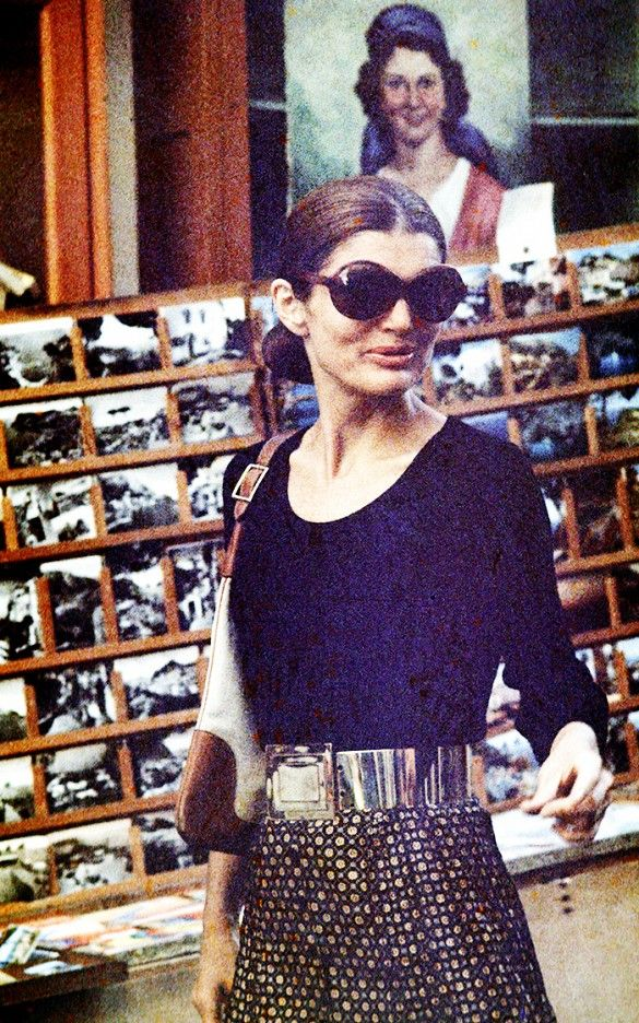 Jackie O wears a black top, printed skirt with a metallic belt, a shoulder bag, and oversized sunglasses