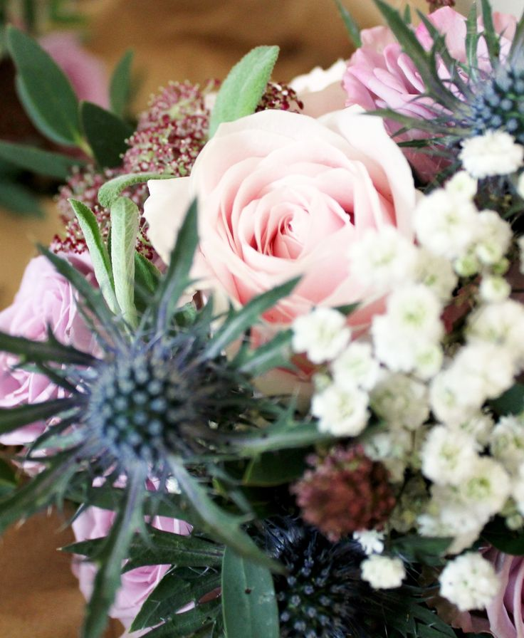 Vintage wedding table centre of mauve armando rose, pink sweet avalanche rose, blue eryngium thistle, gypsophila (baby's breath) and purple daucus carota. Florissimo, Shropshire. (Photo: Maria Worral