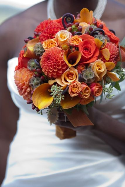 This orange bouquet was created in the fall with local dahlias, orange callas, orange santana roses, mambo spray roses, fiddle head fern, scabiosa pods, seeded euc, orange mokara orchids, and red hypericum.