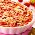 Clafoutis met aardbeien en amandelschilfers Verwarm de oven voor op th. 6 – 180°C. Smeer een niet te hoge, grote ovenschaal in met boter. Snij de aardbeien in stukken, schik ze in de schaal. Doe de bloem en de gemalen amandelen in een grote kom en voeg er geleidelijk aan de melk bij, al roerend met de klopper. Doe er de eieren, de suiker en het zout bij, klop goed. Giet het mengsel op de aardbeien en bak 15 min. in de oven. Bestrooi met de geschaafde amandelen en laat nog 15 min. extra…