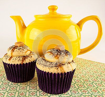 Yellow earthenware teapot with caramel cupcakes on floral print mat.